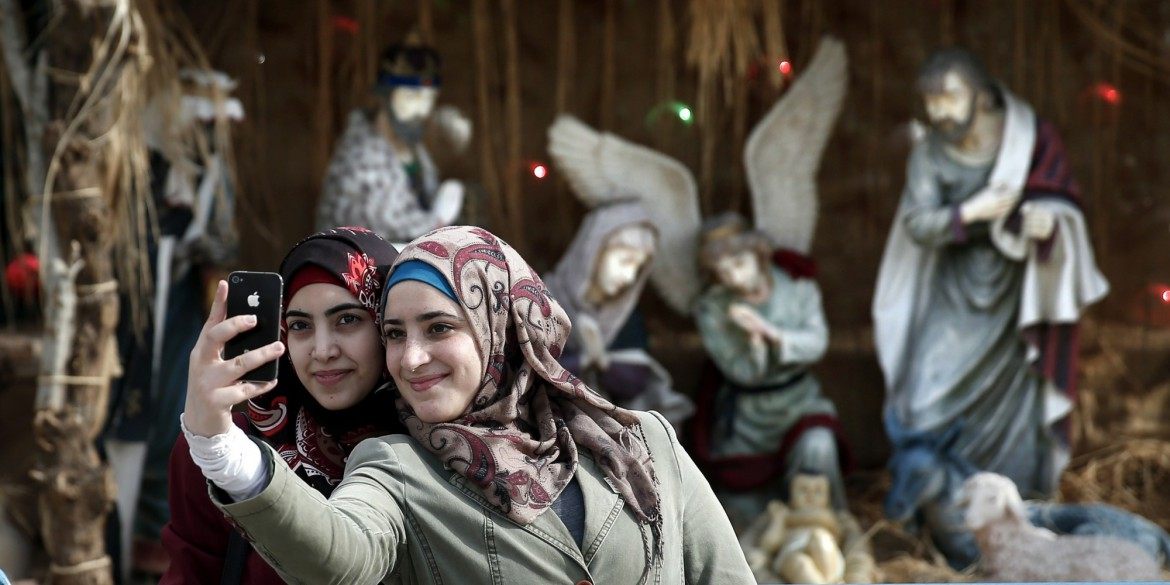 Muslim women take a selfie in front of the giant Christian manger displayed on the Manger Square in front of the Church of the Nativity, revered as the site of Jesus Christ's birth, in the West Bank town of Bethlehem on December 18, 2014, ahead of Christmas celebrations. AFP PHOTO/ THOMAS COEX        (Photo credit should read THOMAS COEX/AFP/Getty Images)