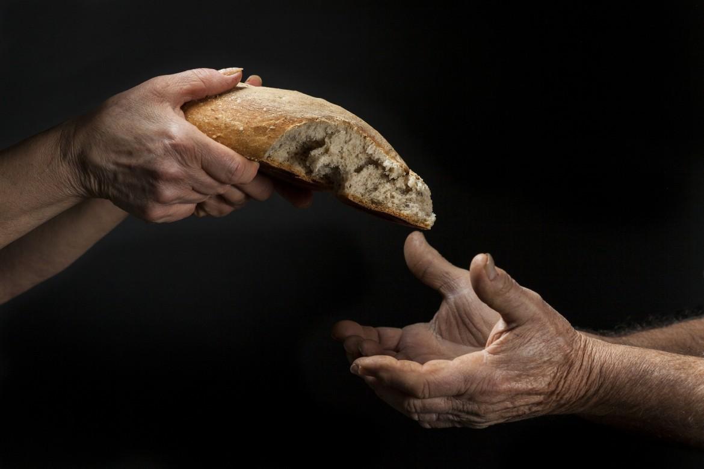 Mano di donna dona pagnotta di pane a un povero senzatetto. Concetto di povert , emarginazione , fame nel mondo